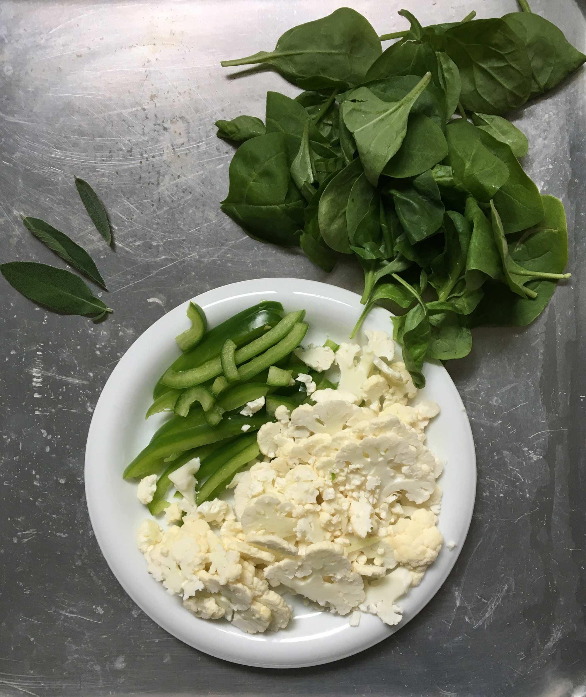Tunt skivad blomkål, grön paprika och färsk spenat.