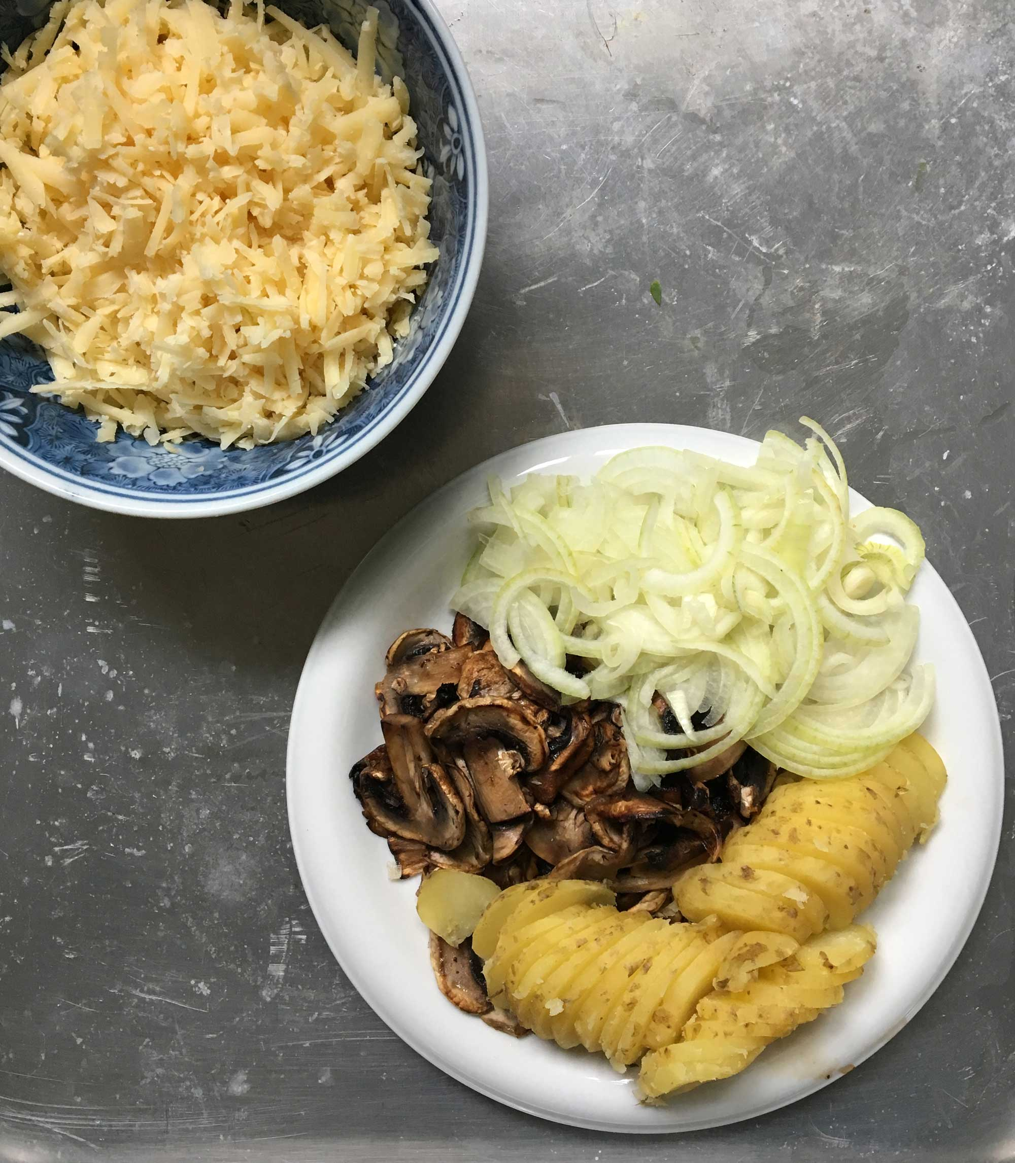 Stekta champinjoner, kokt potatis, skivad lök och västerbottenost.