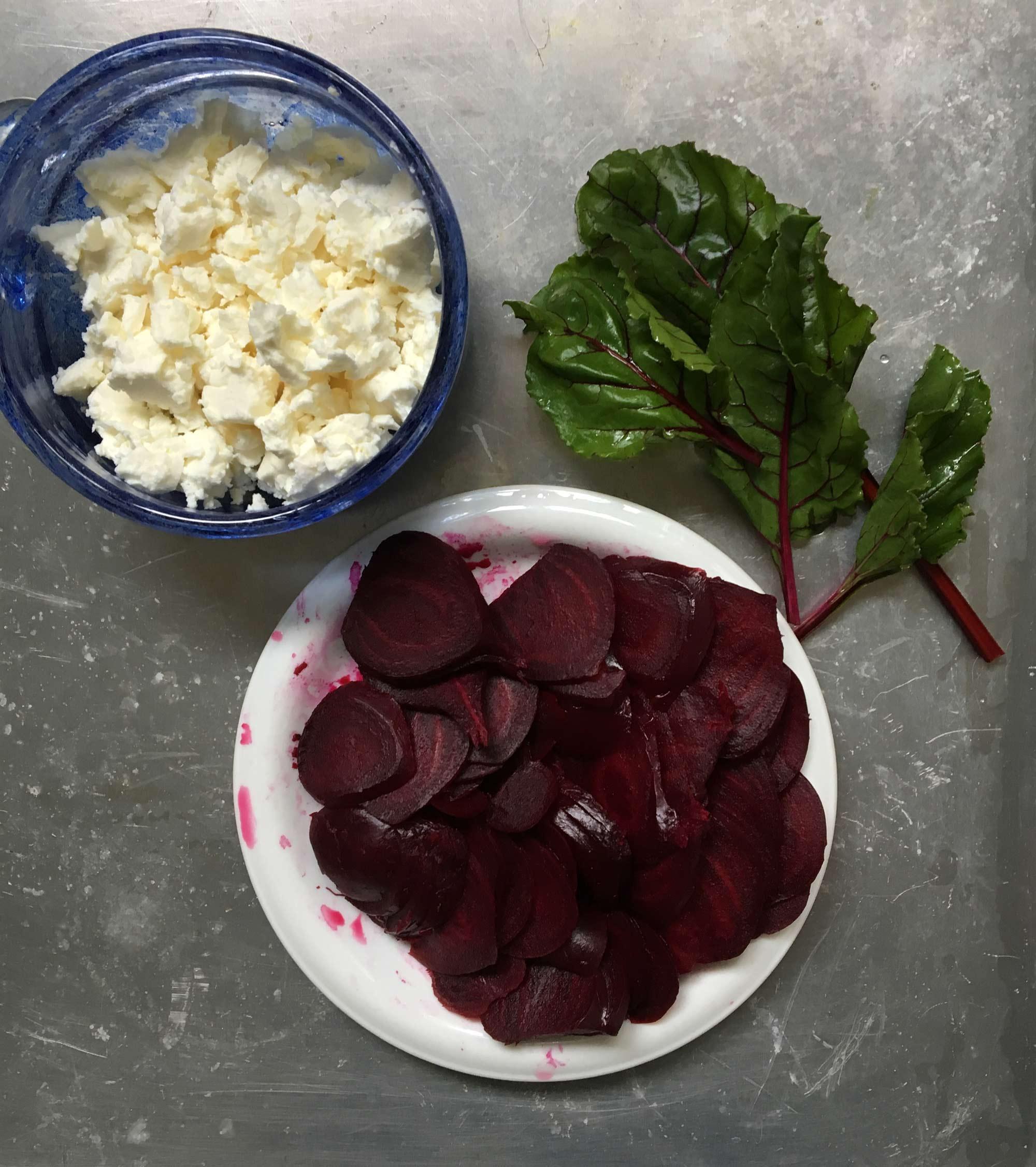 Kokta skivade rödbetor, fetaost och späd rödbetsblast.