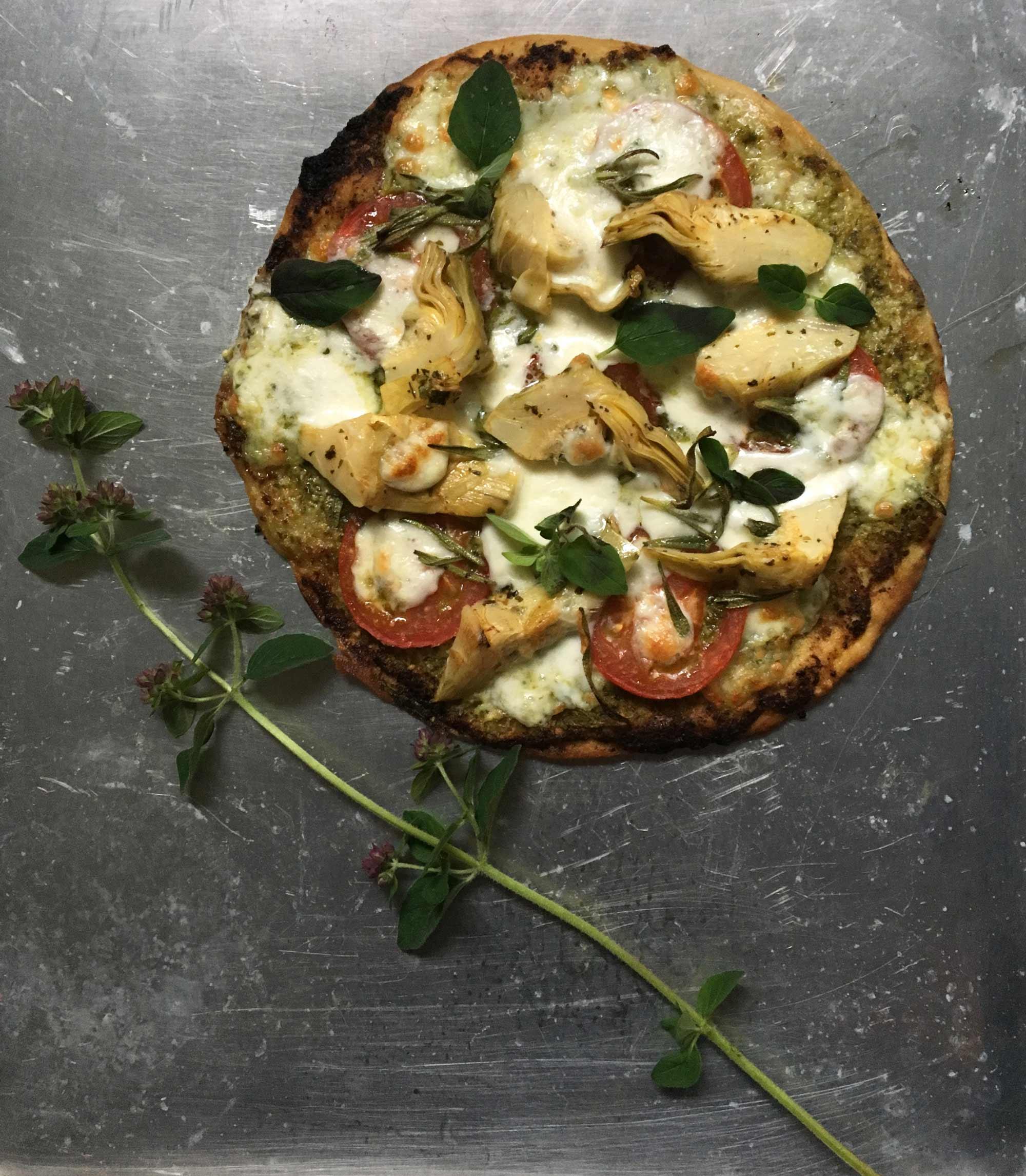 Hemgjord vegopiza med pesto, tomater, kronärtskockshjärtan, mozzarella och oregano.