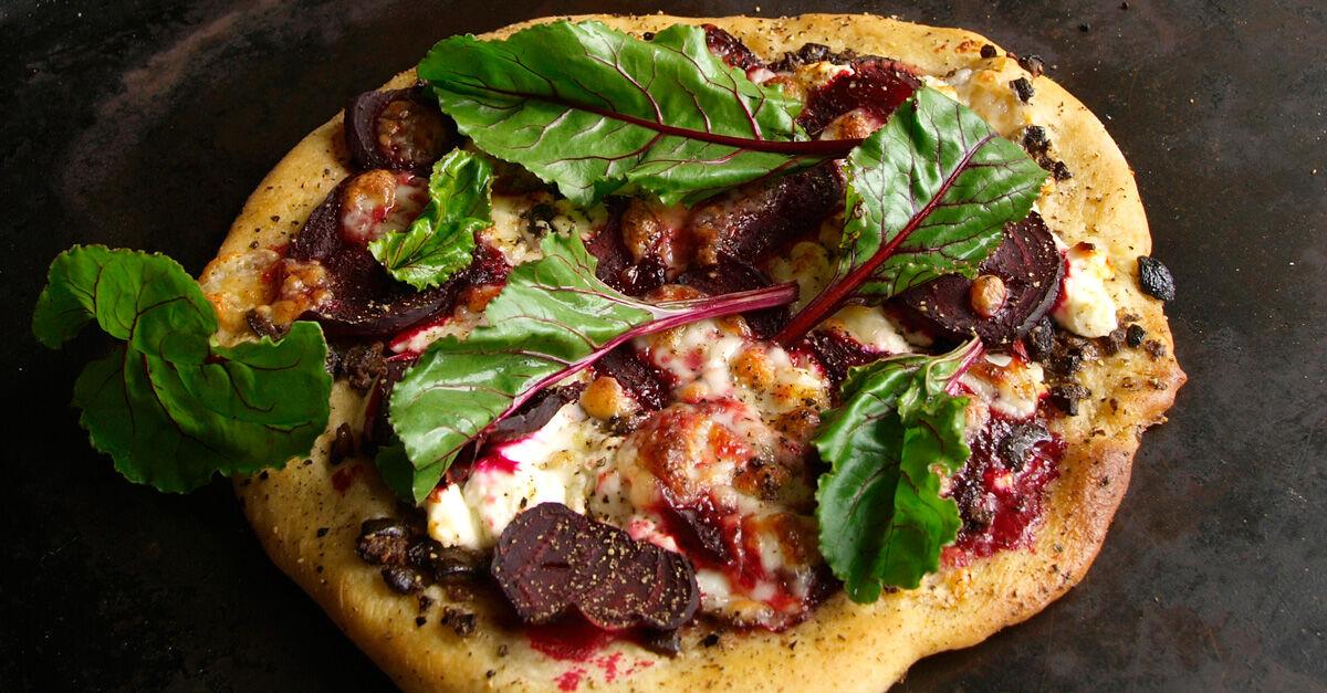 vegetarisk pizza med rödbetor, fetaost, tapenade och rödbetsblad.