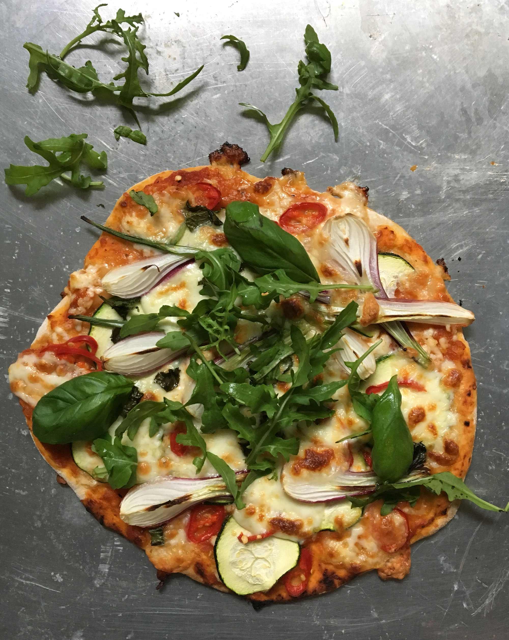 Vegopizza med hemgjord tomatsås, zucchini, chili, färsk lök och rucola.