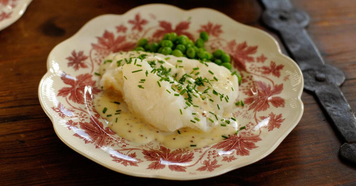 Lutfisk tillagad i ugn och serverad med vitvinssås smaksatt med grov dijonsenap.