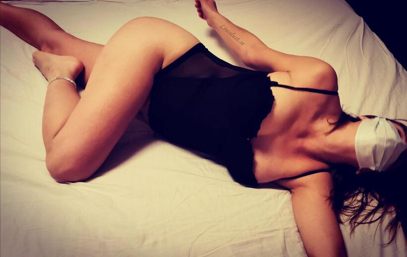 Liw utslagen på sängen med munskydd och korsett