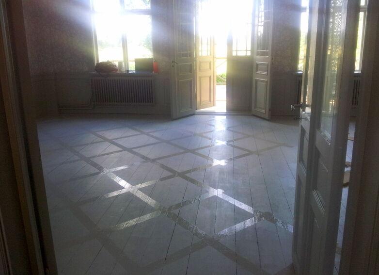 Det här golvet är bara grundmålat med en ljusgrå linoljefärg utspätt med mycket terpentin. Därefter målade jag linjer på fri hand efter blyetslinjer med en något mörkare och outspädd grå färg.  Annelie Beck-Friis på Skagersholm tipsade mig om att göra en mall av en spånskiva vilket verkligen underlättade.