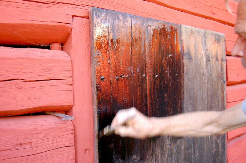 De gamla dörrarna suger, säger Christer.  Det är inte så konstigt att de gör då det säkert är över femtio år sedan de oljades in sist. Troligen var det just tjära med svart pigment som använts, då det var vanligt förr. Att måla med ren tjära är väldigt trögt, men roslagsoljan är perfekt. Och så vackert det blir!