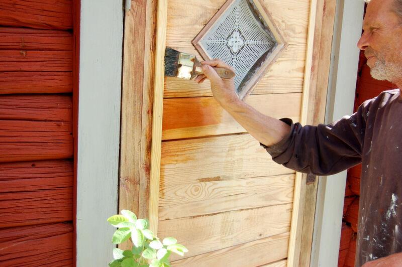 Christer oljar in dörren på kuskbostaden med linolja blandat med 40 % lacknafta innan den ska målas. Dörren hade tidigare en tråkig massonitskiva på framsidan och vi hade tänkt ersätta skivan med pärlspont i fiskbensmönster. Men när vi tog bort skivan hittade vi så fina gamla brädor under att vi beslutat att inte ha någon panel. Jag hoppas nu att länsantikvariet godkänner beslutet.