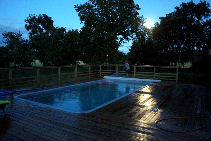 Fullmånen speglar sig i det regnvåta pooldäcket. Lovisa hjälper mig att dra för poolskyddet inför natten.
