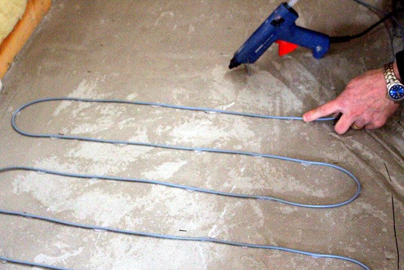 Slingor till elektrisk golvvärme placerades där duschen skulle bli och ännu mer utjämningsmassa fylldes på. Allt var tvunget att luta lagom mot avlopp så att inget vatten skulle bli liggande. Lite knepigt.