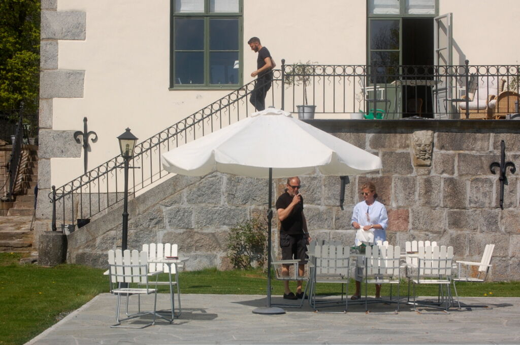 Ann och Sven dukar upp lunch framför poolen.