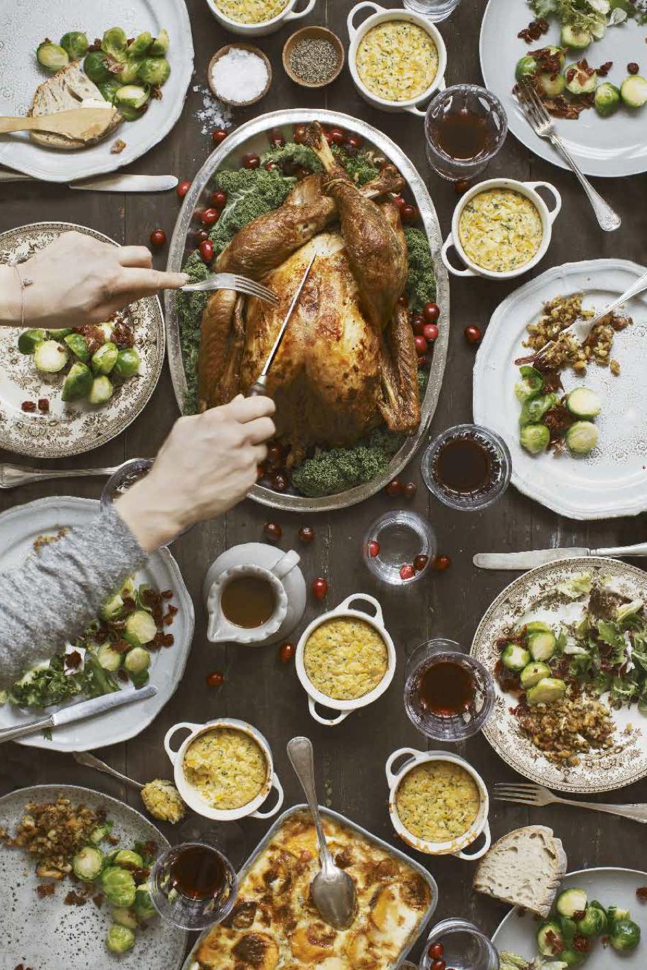 Ett uppdukat bord med heltstekt kalkon och alla andra rätter som serveras till en Thanksgiving middag