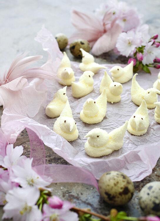 Marshmallowkycklingar på rosa sidenpapper med påskfjädrar