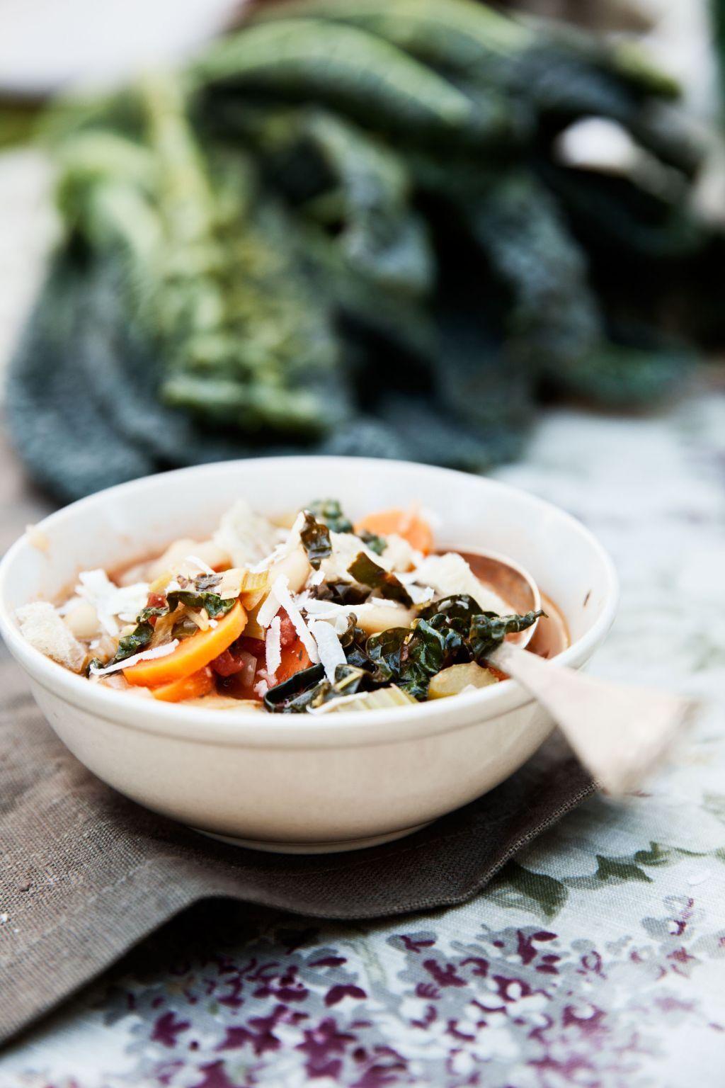 Ribollita soppa  med kål och bönor i en skål på ett träbord med kål som ligger i bakgrunden