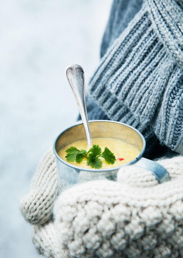 Två händer med vita stickade vantar som håller i en mugg med majssoppa