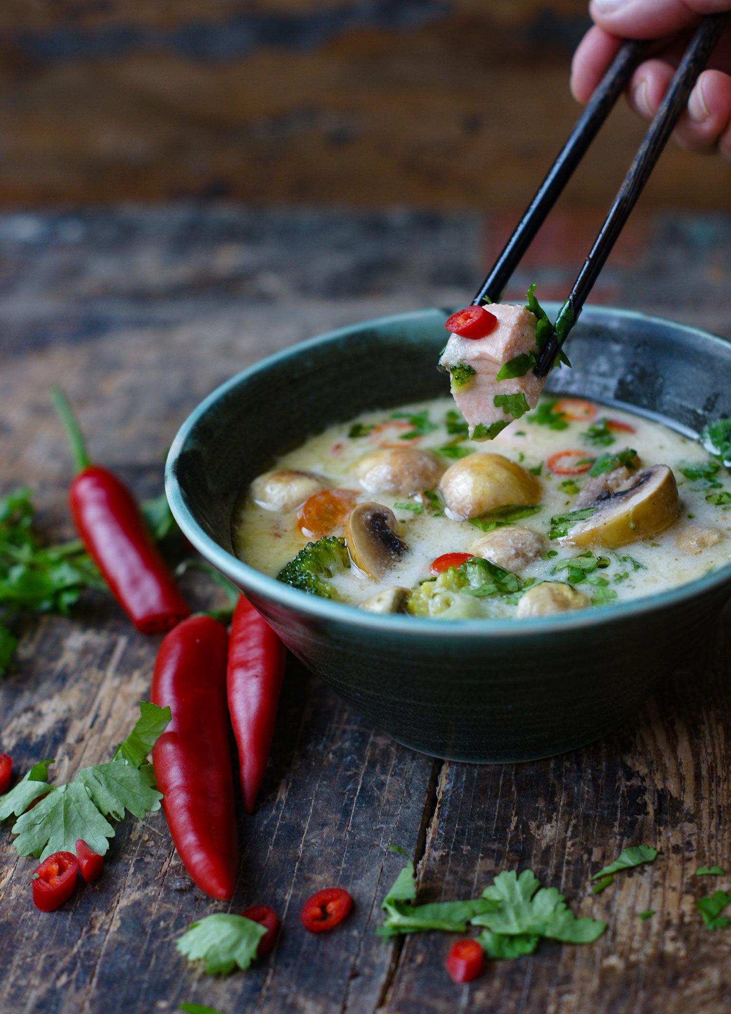 Thai laxsoppa med kokosmjölk, champinjoner, broccoli, chili och lime i en rustik skål på ett rustikt träbord. Runtomkring skålen ligger chili och koriander.