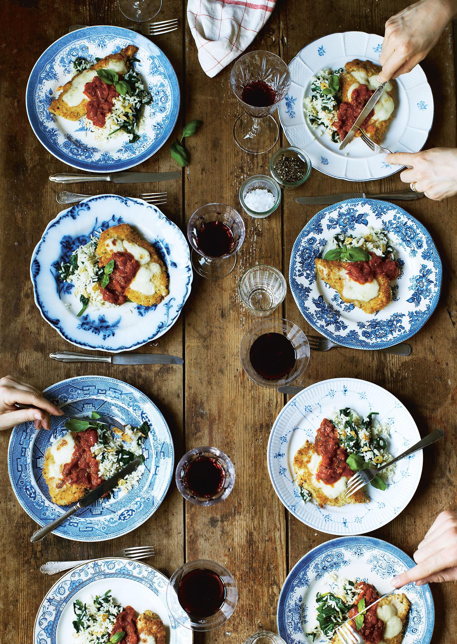 En tallrik kyckling parmigiana på ett träbord med ett glas rött vin