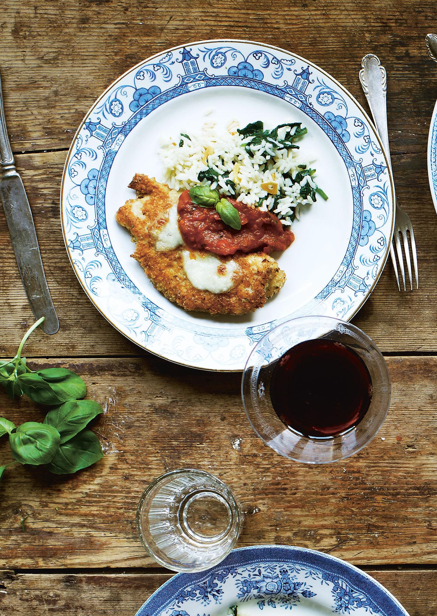 Ett bord med flera personer som äter kyckling parmigiana och dricker rött vin