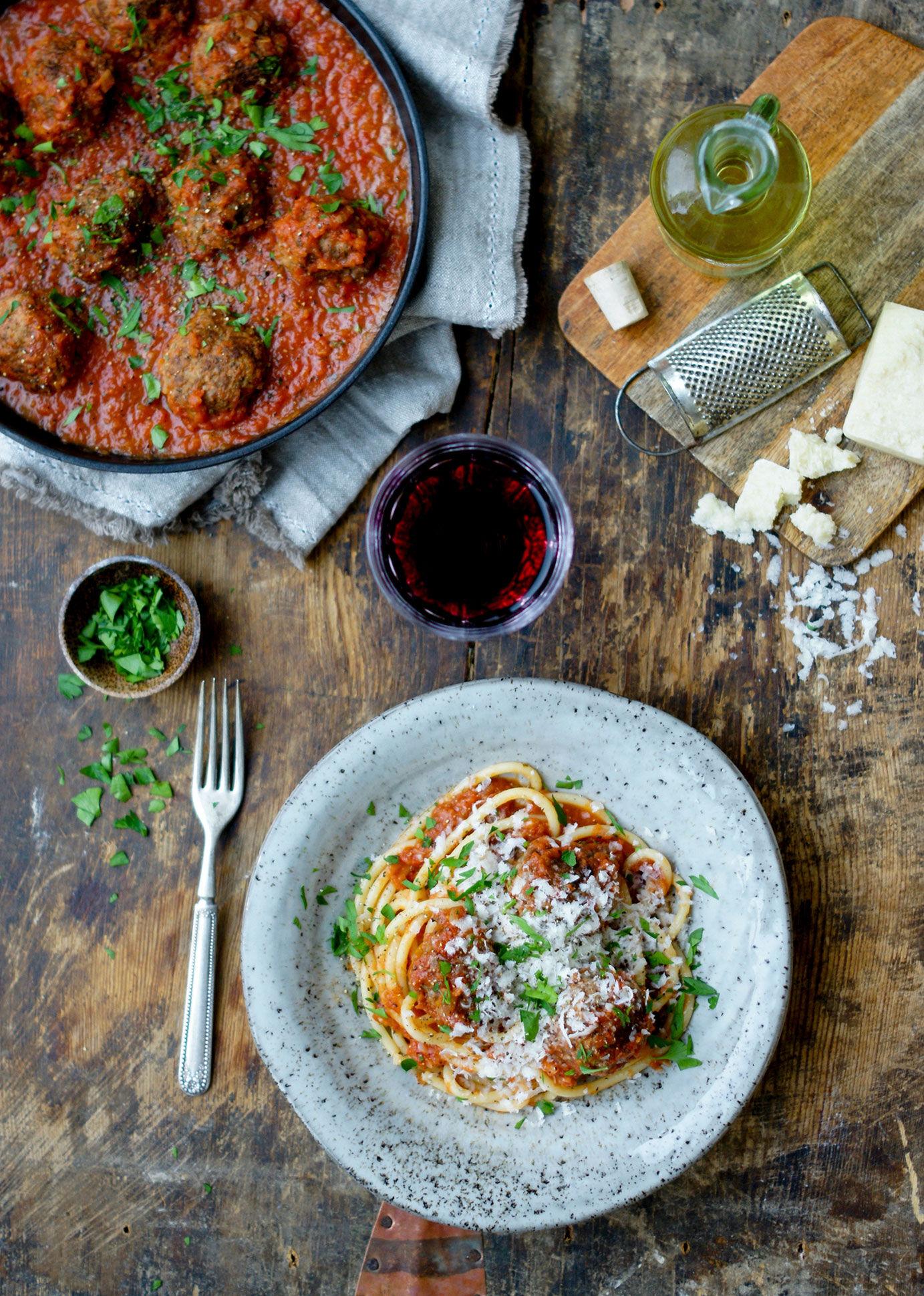 italienska köttbullar i tomatsås med spaghetti uppdukad på träbord