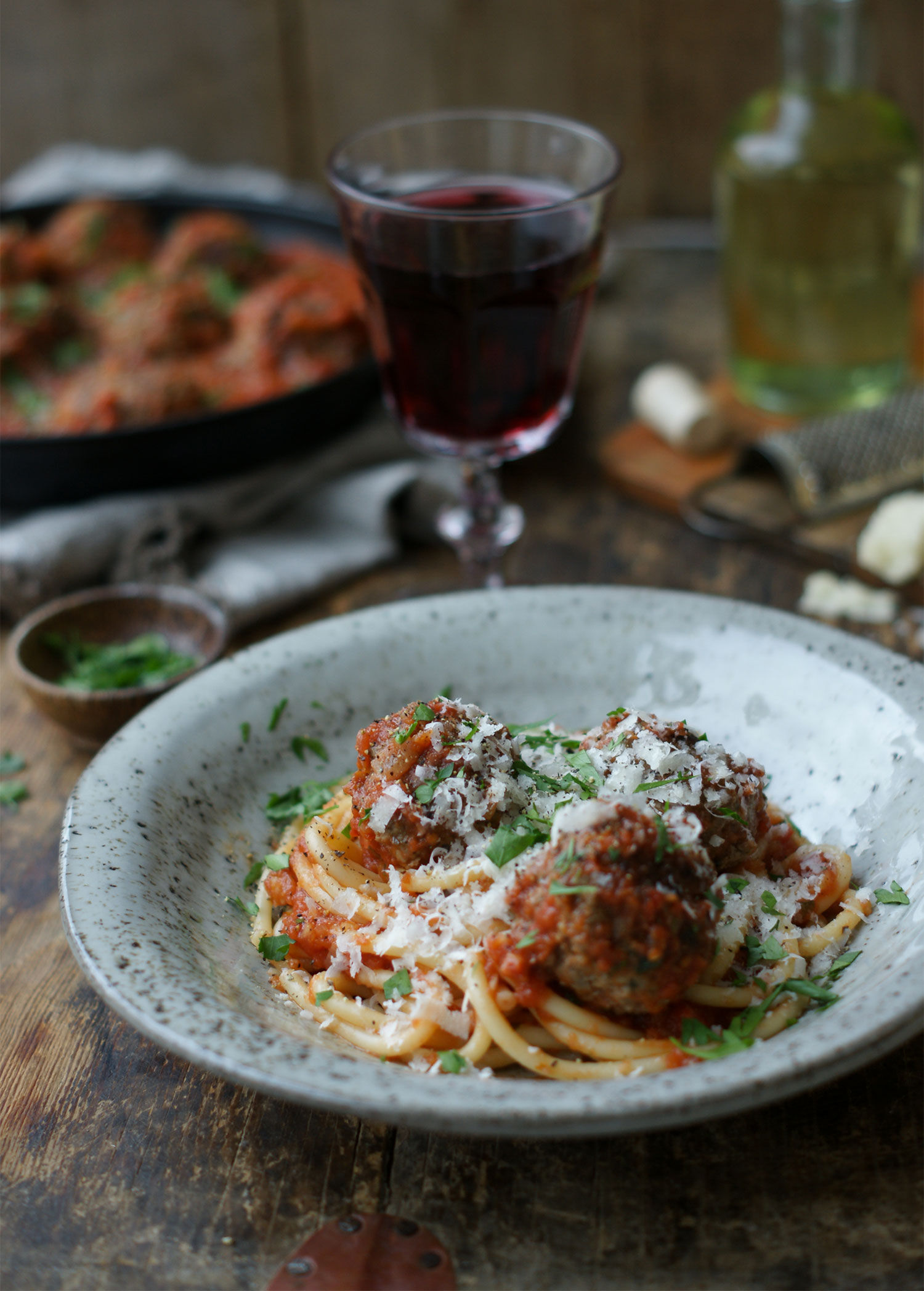Spaghetti på gaffel med italienska köttbullar i tomatsås uppdukat på ett bord