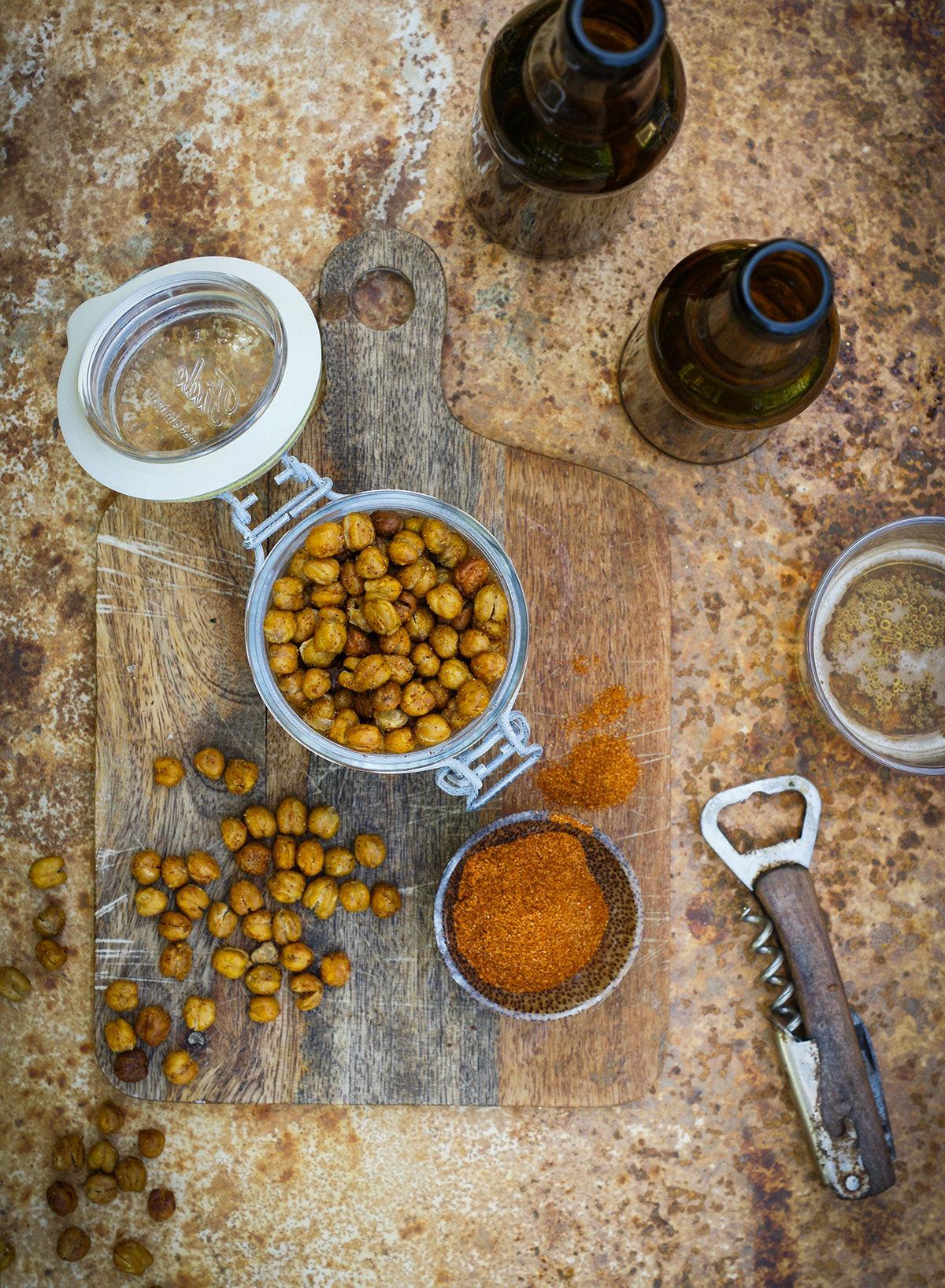 Kryddiga och krispiga rostade kikärtor på ett träbord med öl
