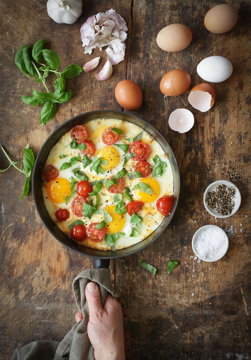 Allt-i-ett mozzarella, tomater och ägg i gjutjärnspanna på träskiva