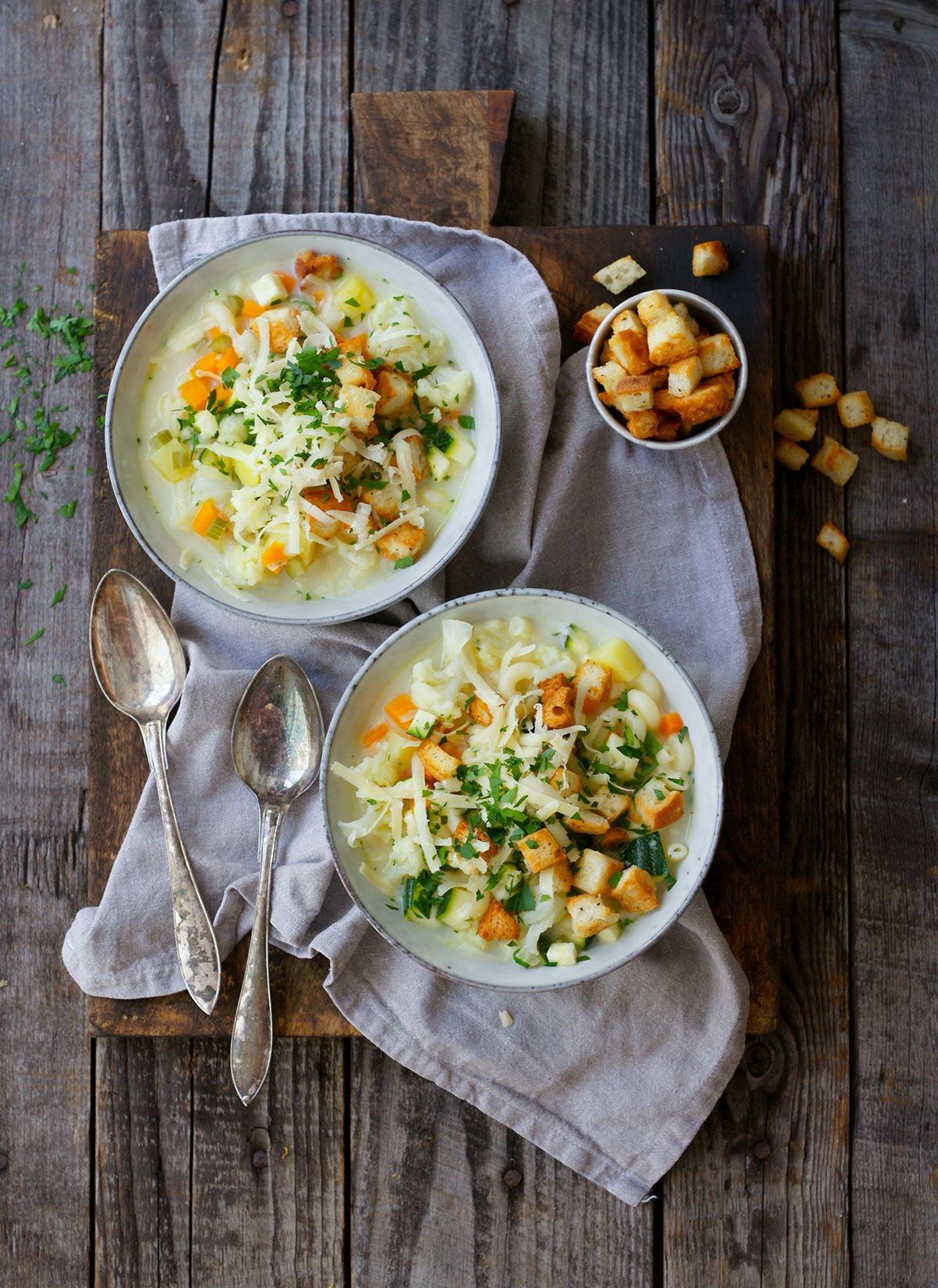 Grönsakssoppa med makaroner, örtkrutonger och Gruyére-ost i två skålar på ett träbord