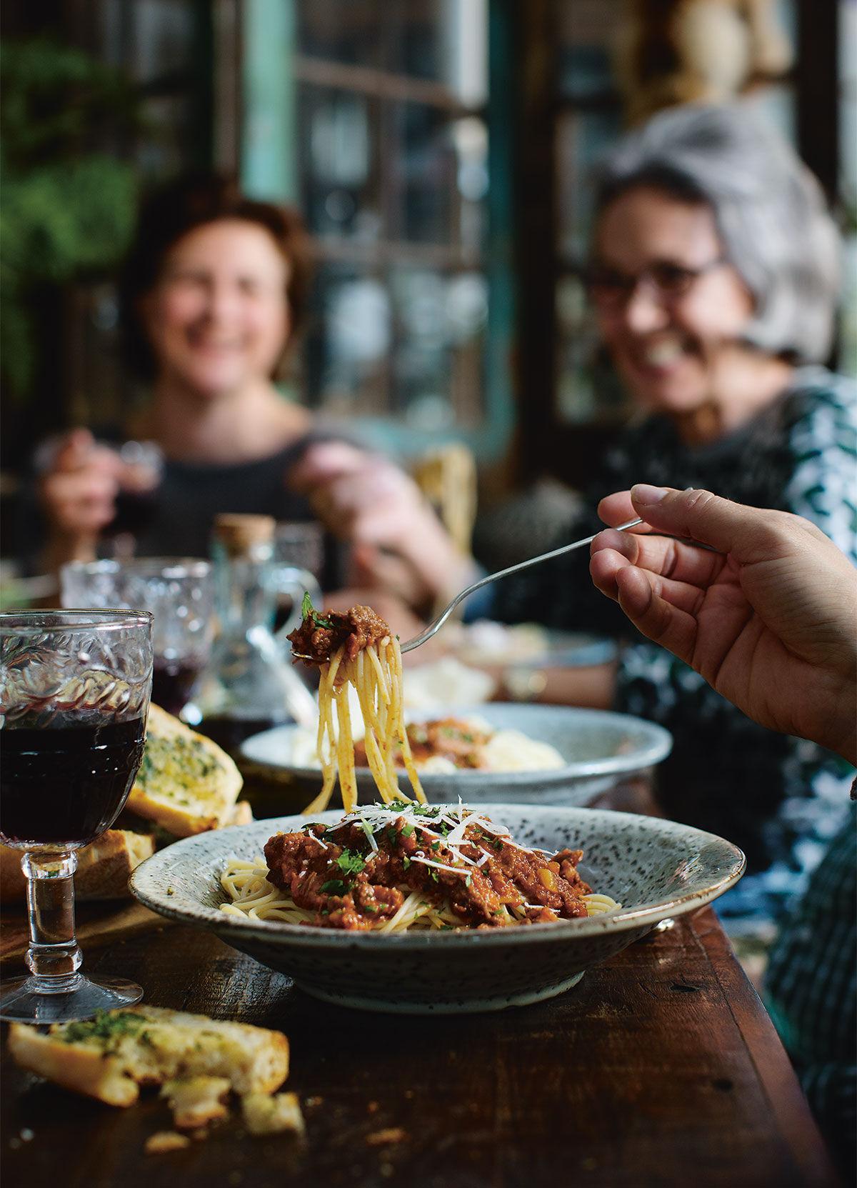 Familj och vänner runt middagsbordet som äter Bolognese Ragù med rostad baguette med vitlök- och sardellsmör