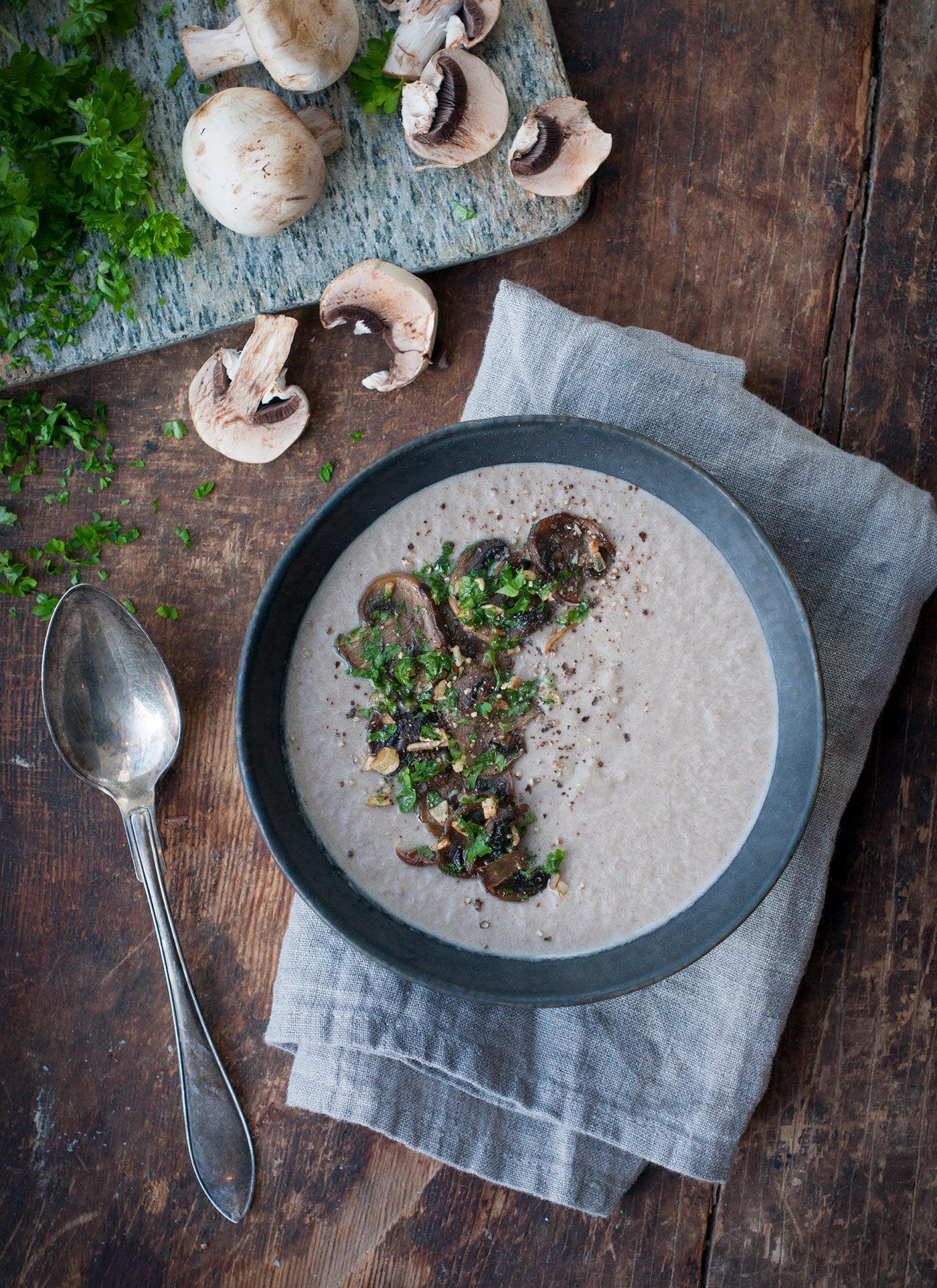 Krämig champinjonsoppa i en skål på ett rustikt träbord och en linneservett.