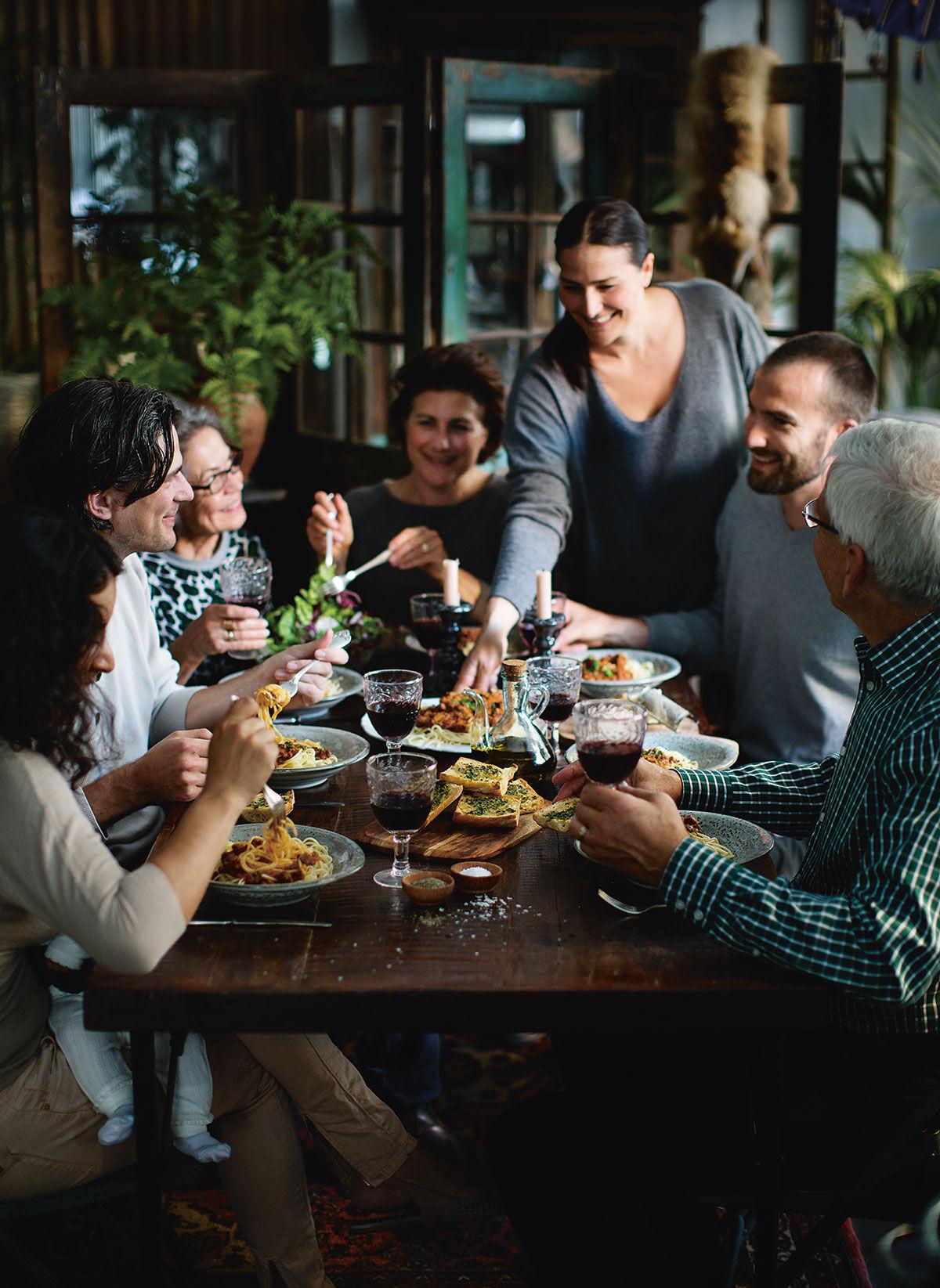 Familj och vänner runt matbordet som äter Bolognese Ragù med rostad baguette med vitlök- och sardellsmör