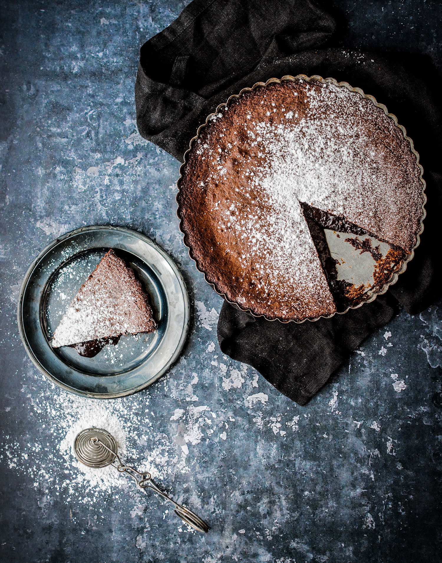 God och kladdig chokladkladdkaka med en utskuren bit på ett rustikt plåtunderlag och svart linneservett. Matstylist Monica Eisenman