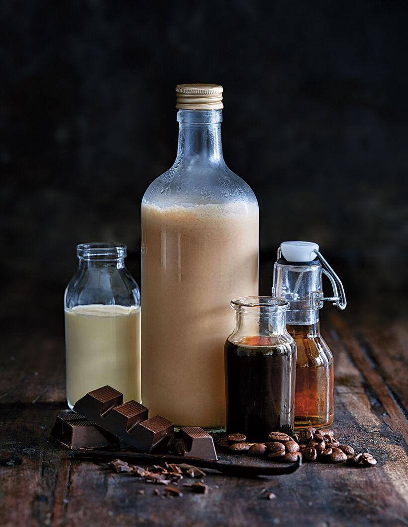 Ingredienserna till hemgjord Baileys i små glasflaskor samt strödd runt flaskorna på ett mörkt och rustikt träbord