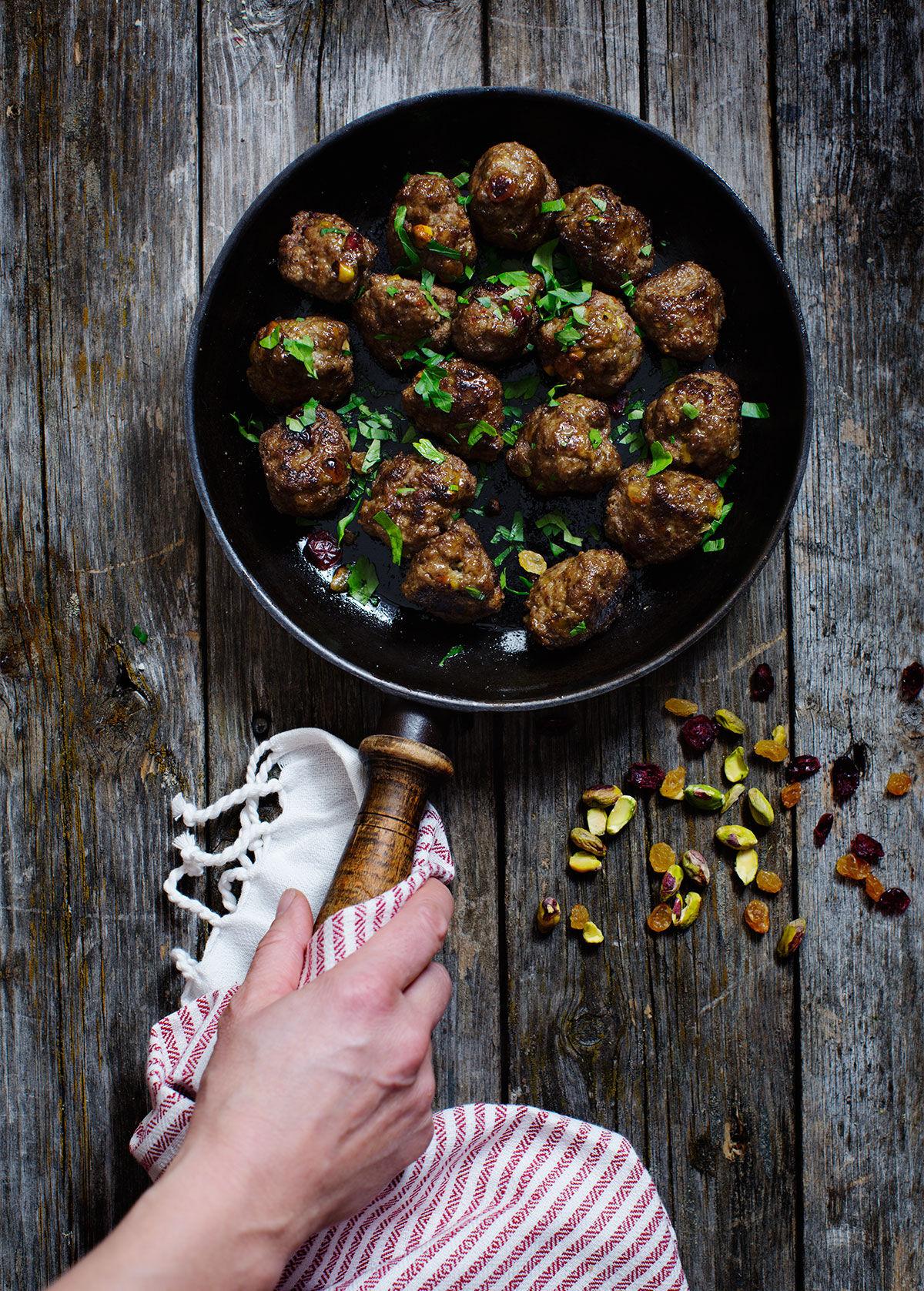 Kryddiga köttbullar med pistagenötter, russin och tranbär i en gjutjärnspanna