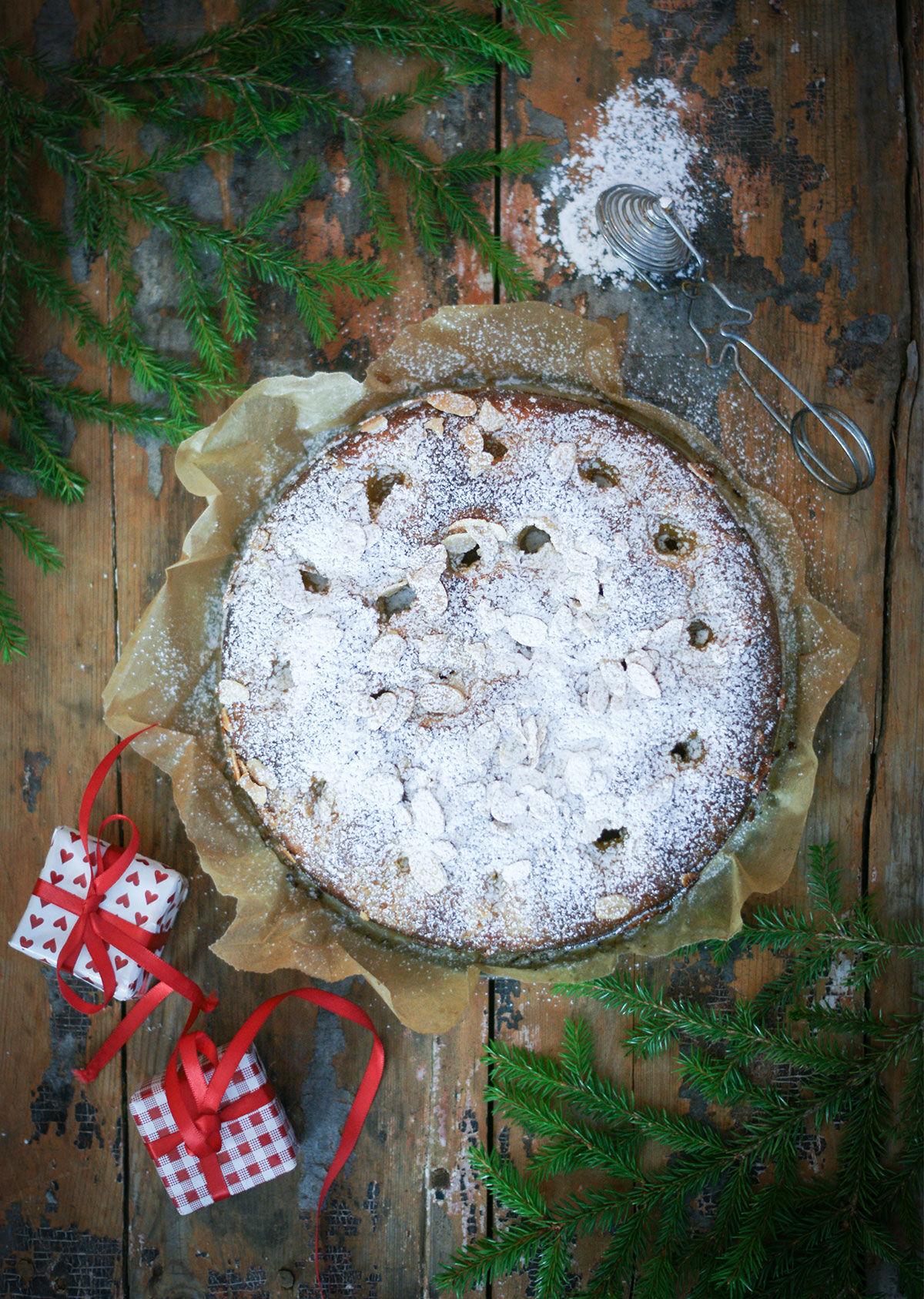 Saffranskaka med vaniljkräm på träbord, med granris och små julklappar