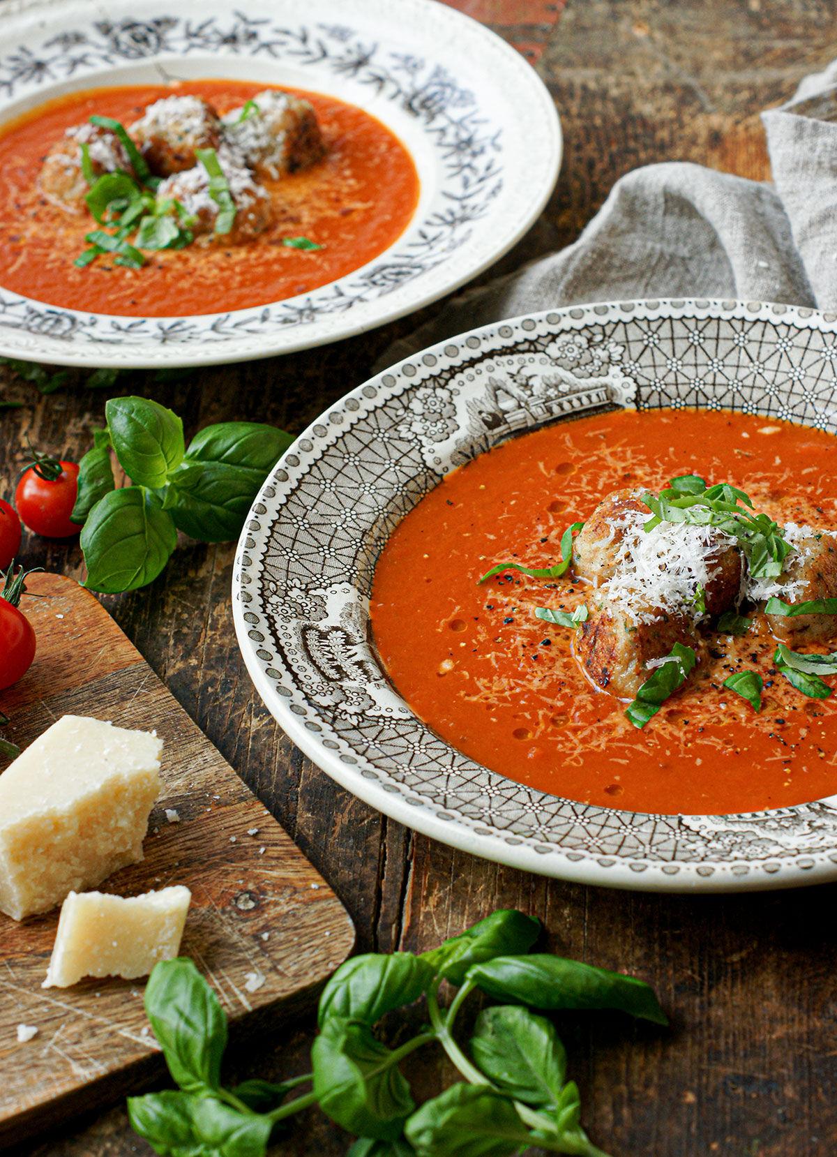 Italiensk soppa med parmesan- och kycklingbollar i djup tallrik på ett träbord