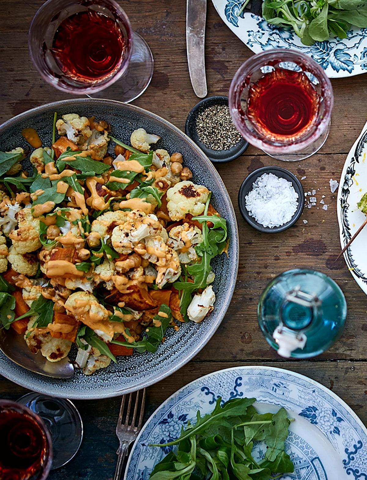 Ugnsbakad sötpotatis, blomkål och kikärtor med tahini-harissa dressing upplagt på ett dukat träbord