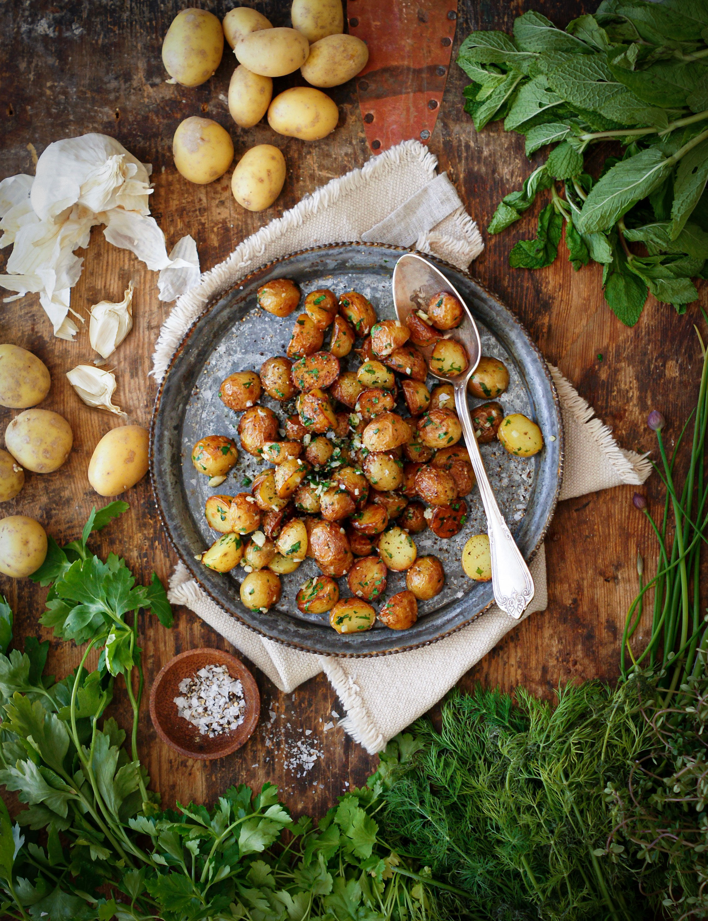 Smörstekt potatis med vitlök och persilja på ett fat på ett träbord med massa färska örter