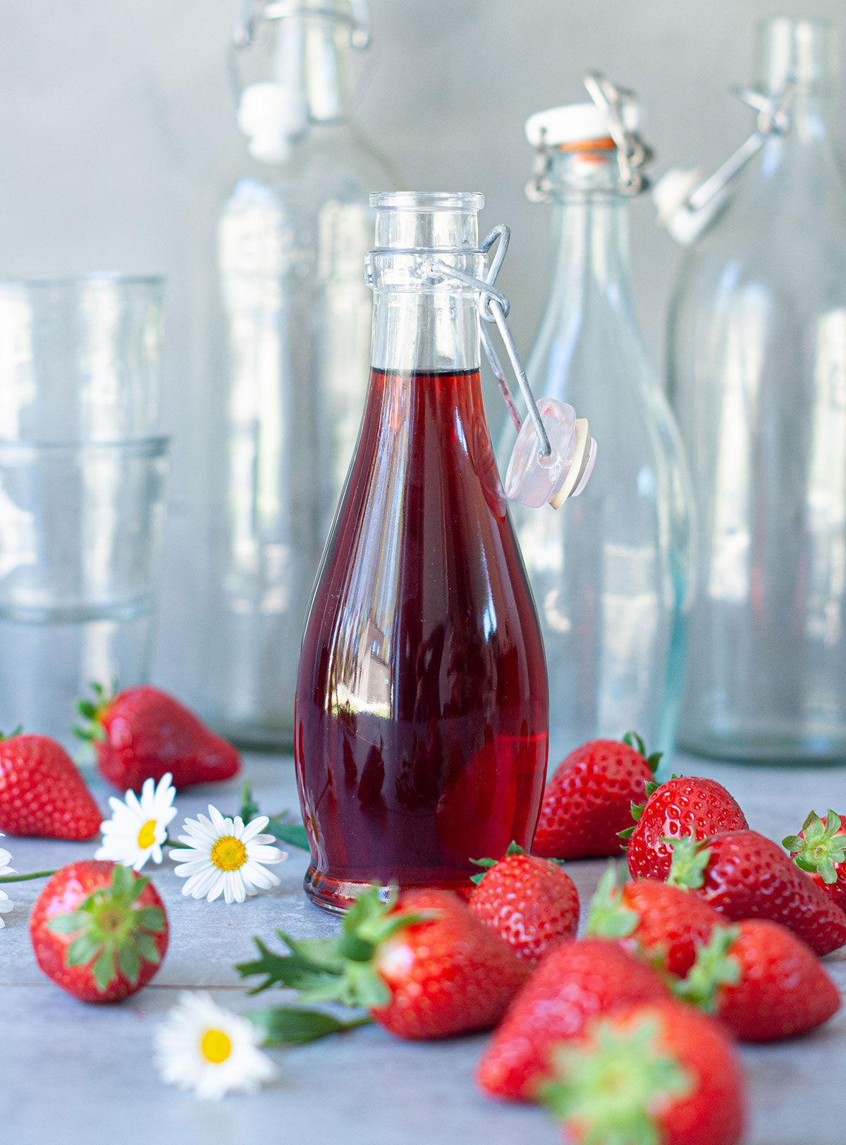 Flaska med jordgubbssaft omringad av färska jordgubbar