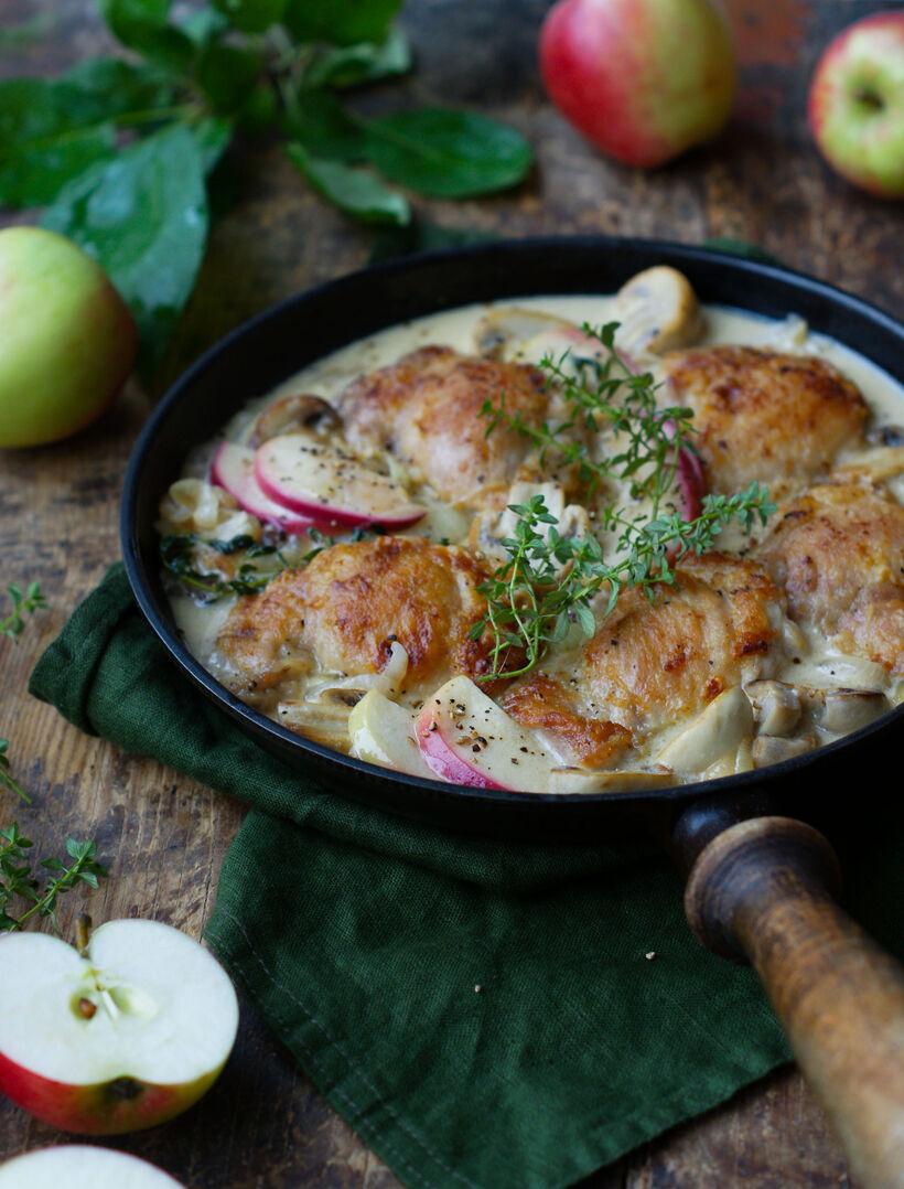 Kyckling i cidersås med champinjoner och äpple i gjutjärnspanna på träskiva