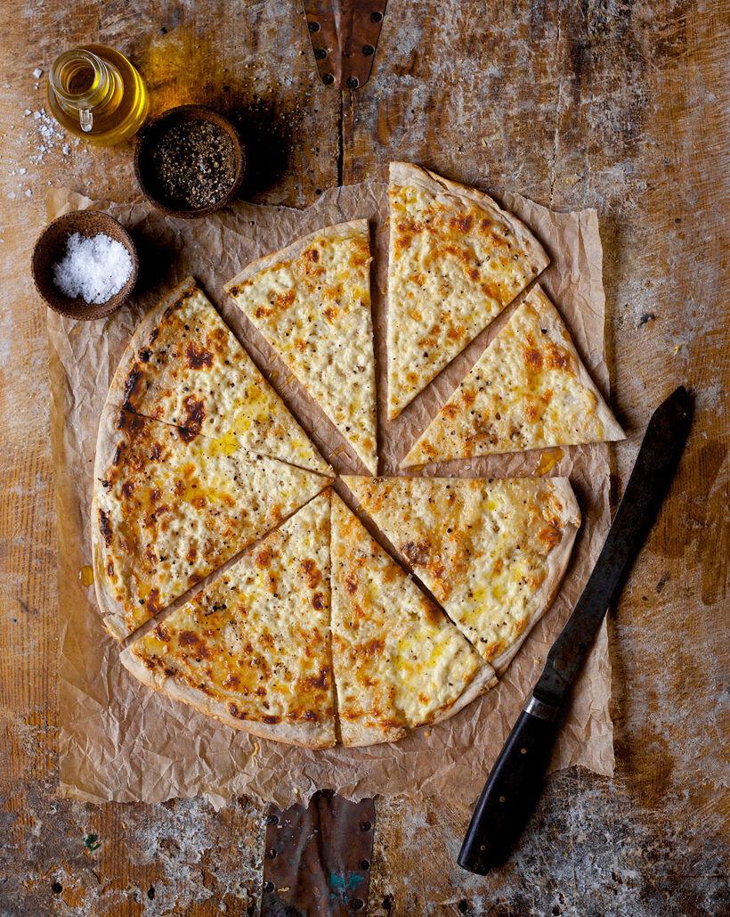 Liba-pizza med Västerbottensost och svart peppar uppskuren på ett rustikt träbord