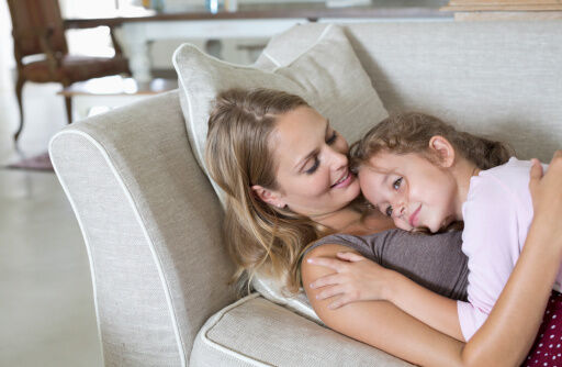 Mother and daughter relaxing on sofa